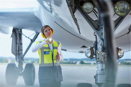 Ground crew worker under airplane with flashlight on airport tarmac Stock Photo - Premium Royalty-Free, Code: 6113-08784282
