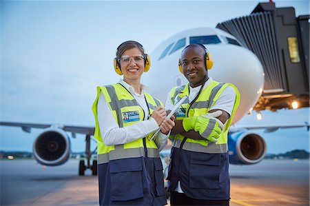 security - Portrait confident air traffic control ground crew workers near airplane on airport tarmac Stock Photo - Premium Royalty-Free, Code: 6113-08784320