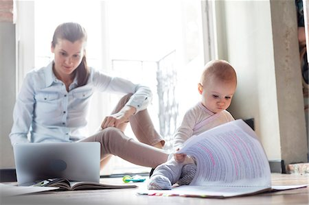 Curious baby daughter looking at paperwork next to mother working at laptop Stock Photo - Premium Royalty-Free, Code: 6113-08784443