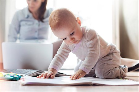 Baby girl playing on floor near mother working on laptop Stock Photo - Premium Royalty-Free, Code: 6113-08784413