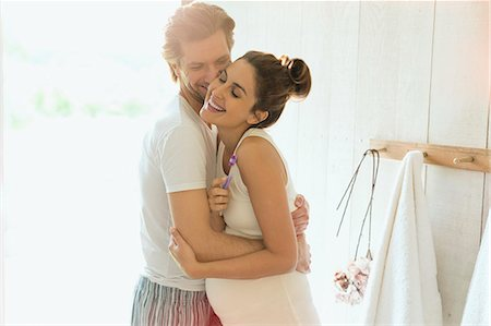 romance - Affectionate pregnant couple hugging in sunny bathroom Stock Photo - Premium Royalty-Free, Code: 6113-08722075