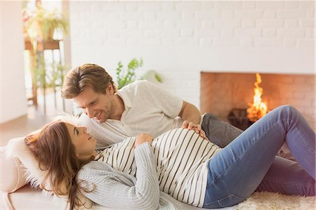 relationship - Pregnant couple laying and talking near fireplace in living room Stock Photo - Premium Royalty-Free, Code: 6113-08722020