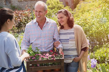Plant nursery worker helping smiling couple with flowers in garden Stock Photo - Premium Royalty-Free, Code: 6113-08722193