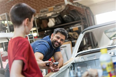 Smiling father taking tool from son in auto repair shop Stock Photo - Premium Royalty-Free, Code: 6113-08722263