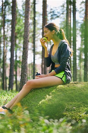 Runner resting eating apple on mossy rock in woods Stock Photo - Premium Royalty-Free, Code: 6113-08722212