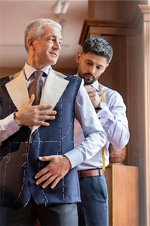 Tailor fitting businessman for suit in menswear shop Foto de stock - Sin royalties Premium, Código: 6113-08722364