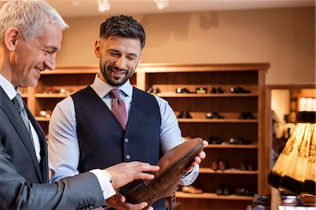 Worker showing dress shoes to businessman in menswear shop Stock Photo - Premium Royalty-Free, Code: 6113-08722366
