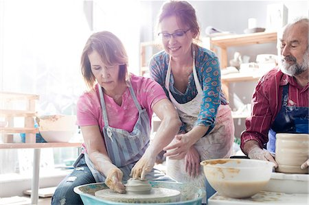 Teacher guiding mature student using pottery wheel in studio Stock Photo - Premium Royalty-Free, Code: 6113-08722370