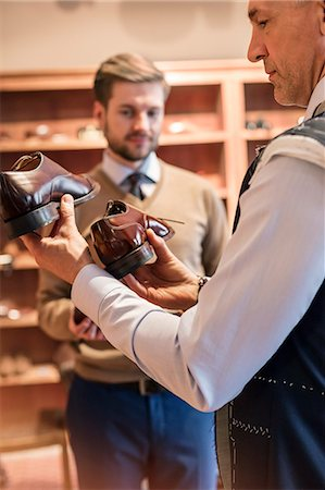 Businessman shopping for dress shoes in menswear shop Stock Photo - Premium Royalty-Free, Code: 6113-08722319