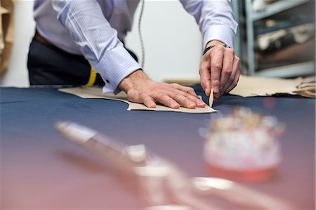 Tailor marking fabric in menswear workshop Stock Photo - Premium Royalty-Free, Code: 6113-08722323