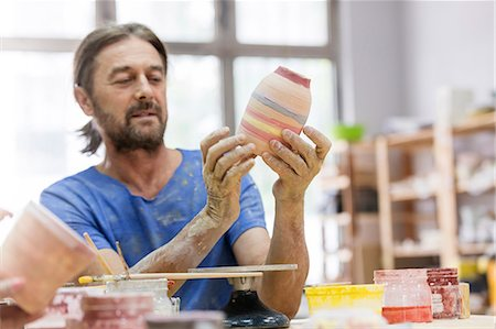 Mature man painting pottery vase in studio Stock Photo - Premium Royalty-Free, Code: 6113-08722460
