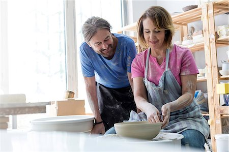 Mature couple using pottery wheel in studio Stock Photo - Premium Royalty-Free, Code: 6113-08722464