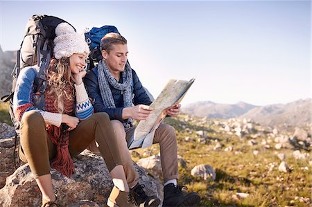 Young couple with backpacks hiking, resting and checking map on sunny rocks Stock Photo - Premium Royalty-Free, Code: 6113-08882830