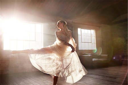 Graceful female dancer dancing in sunny studio Stock Photo - Premium Royalty-Free, Code: 6113-08805527