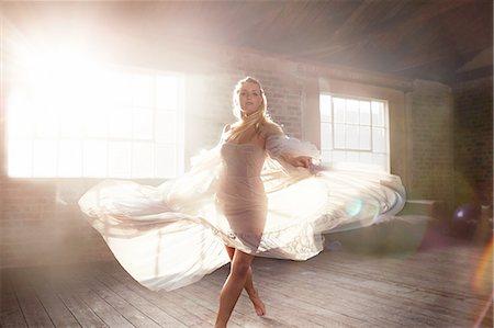 Graceful young female dancer dancing in sunny studio Stock Photo - Premium Royalty-Free, Code: 6113-08805529