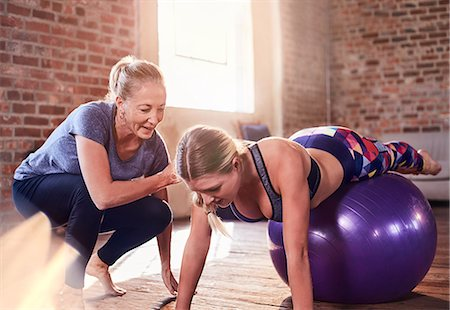 Fitness instructor helping young woman balancing on fitness ball in gym studio Stock Photo - Premium Royalty-Free, Code: 6113-08805530