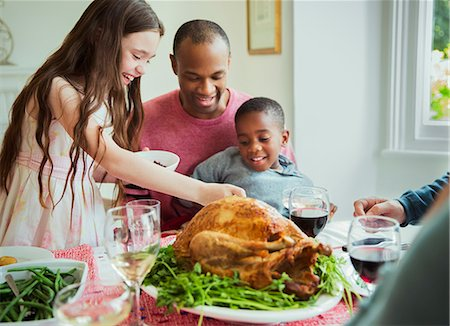 Multi-ethnic family enjoying Christmas turkey dinner at table Stock Photo - Premium Royalty-Free, Code: 6113-08805684