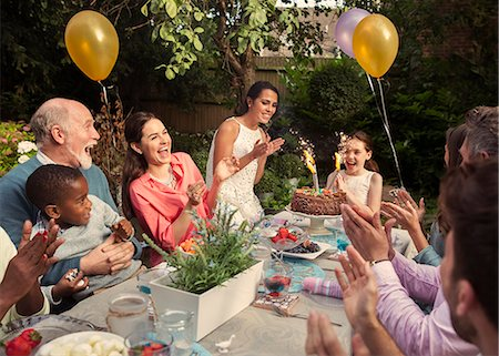 Multi-ethnic multi-generation family clapping celebrating birthday with fireworks cake at patio table Stock Photo - Premium Royalty-Free, Code: 6113-08805685