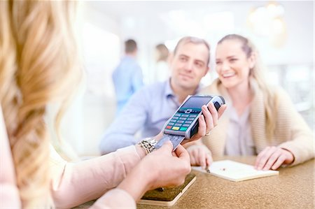 Couple paying for jewelry watching jeweler using credit card reader Stock Photo - Premium Royalty-Free, Code: 6113-08805727
