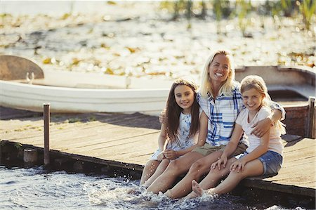 preteen girl feet - Portrait happy mother and daughters on dock splashing feet in lake Stock Photo - Premium Royalty-Free, Code: 6113-08909885