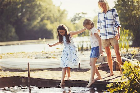 preteen girl feet - Mother watching daughters sticking toes in water on lakeside dock Stock Photo - Premium Royalty-Free, Code: 6113-08909946