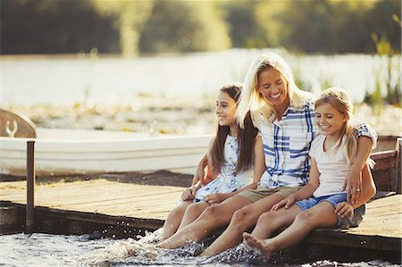 preteen girl feet - Smiling, affectionate mother and daughters on dock splashing feet in lake Stock Photo - Premium Royalty-Free, Code: 6113-08909903