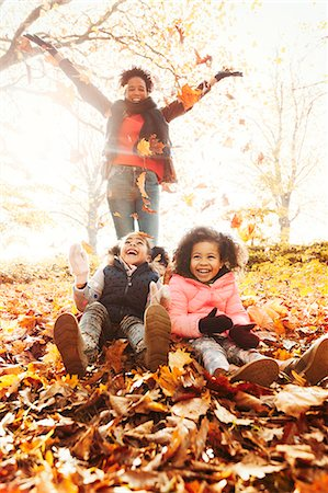 pile leaves playing - Playful mother and daughters throwing autumn leaves in sunny park Stock Photo - Premium Royalty-Free, Code: 6113-08910147