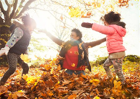 pile leaves playing - Playful mother and daughters throwing autumn leaves in sunny park Stock Photo - Premium Royalty-Free, Code: 6113-08910176