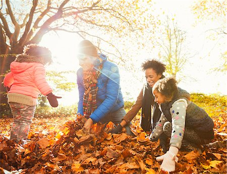 pile leaves playing - Young family playing in autumn leaves in sunny park Stock Photo - Premium Royalty-Free, Code: 6113-08910186