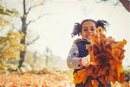 pile leaves playing - Portrait smiling girl holding autumn leaves in park Stock Photo - Premium Royalty-Free, Code: 6113-08910101