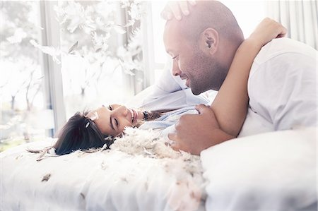 romantic couple bed - Pillow feathers falling around playful, affectionate couple on bed Stock Photo - Premium Royalty-Free, Code: 6113-08910234