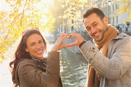 Portrait smiling young couple forming heart-shape with hands at sunny autumn canal Stock Photo - Premium Royalty-Free, Code: 6113-08927658