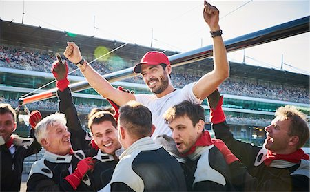 Formula one racing team carrying driver on shoulders, celebrating victory Stock Photo - Premium Royalty-Free, Code: 6113-08927838