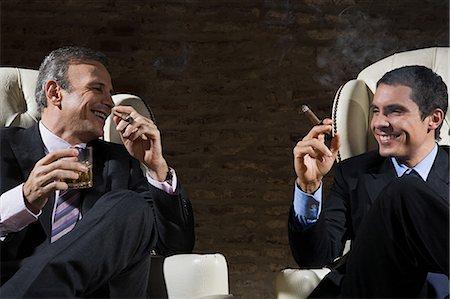 Businessmen smoking cigars Stock Photo - Premium Royalty-Free, Code: 6114-06591388