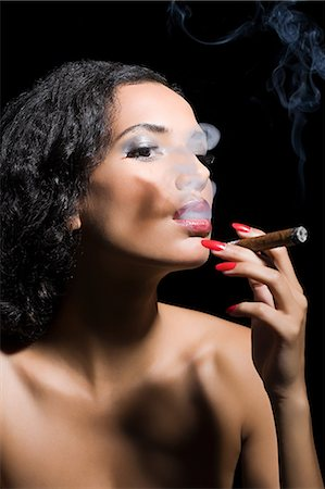 Beautiful woman smoking a cigar Stock Photo - Premium Royalty-Free, Code: 6114-06593645