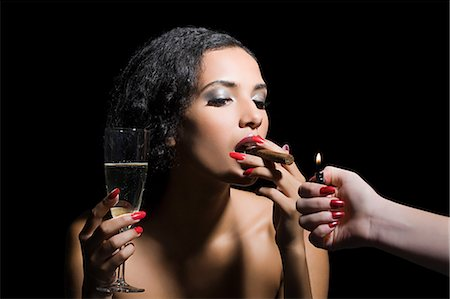 Woman lighting a cigar Stock Photo - Premium Royalty-Free, Code: 6114-06593625