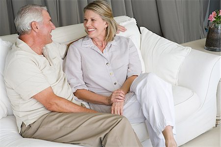 Senior man and mature women sitting together and laughing on sofa Stock Photo - Premium Royalty-Free, Code: 6114-06595829