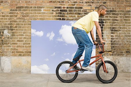 Young man on bicycle by sky backdrop Stock Photo - Premium Royalty-Free, Code: 6114-06596539
