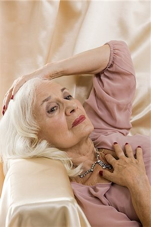 Glamorous senior woman lying on satin Stock Photo - Premium Royalty-Free, Code: 6114-06596664