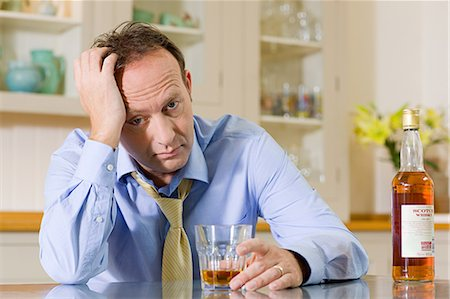 Stressed man with whisky Stock Photo - Premium Royalty-Free, Code: 6114-06596781