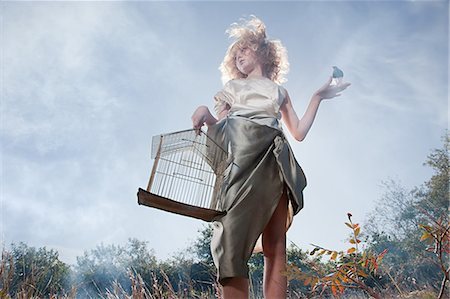 Girl with a bird and cage Stock Photo - Premium Royalty-Free, Code: 6114-06597087