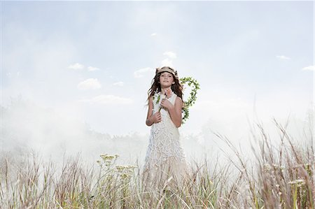 Girl dressed as fairy in field with flower Stock Photo - Premium Royalty-Free, Code: 6114-06597089