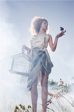 Girl with a bird and cage Stock Photo - Premium Royalty-Free, Code: 6114-06597100