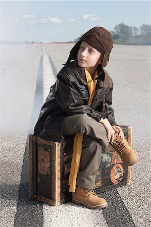 Boy sitting on suitcase on runway Stock Photo - Premium Royalty-Free, Code: 6114-06597104
