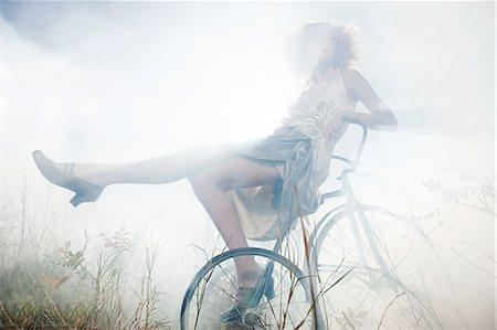 Girl sitting on bike in mist Stock Photo - Premium Royalty-Free, Code: 6114-06597106