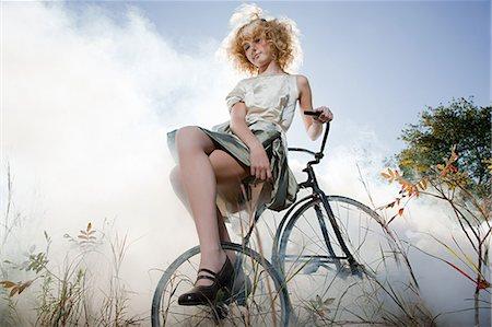 Girl sitting on bicycle Stock Photo - Premium Royalty-Free, Code: 6114-06597109