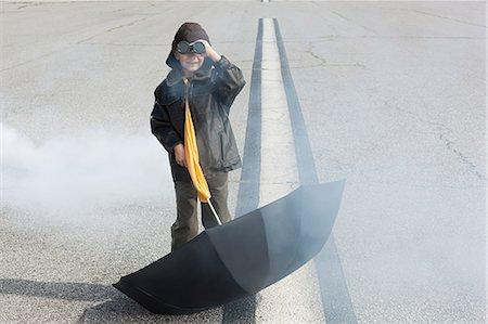 Boy on runway with binoculars and umbrella Stock Photo - Premium Royalty-Free, Code: 6114-06597110