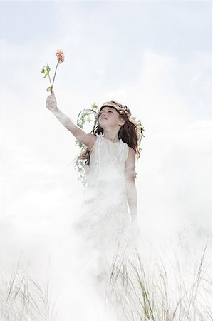 Girl dressed as fairy with flower Stock Photo - Premium Royalty-Free, Code: 6114-06597115