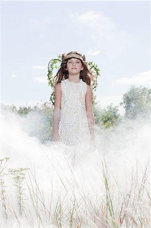 Girl dressed as fairy in cloud of smoke Stock Photo - Premium Royalty-Free, Code: 6114-06597128
