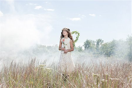 Girl dressed as fairy in field with flower Stock Photo - Premium Royalty-Free, Code: 6114-06597130